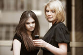 Young women looking at mobile phone — Stock Photo