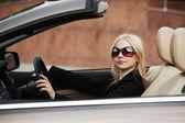 Young woman driving a convertible car — ストック写真