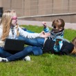 Teenage school girls lying on a grass — Stock Photo