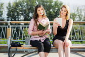 Young women with a book and digital tablet computer — Stock Photo