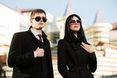 Young business couple walking on the city street — Стоковое фото