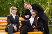 Young business people using laptop in a city park — 图库照片