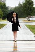 Happy woman with umbrella walking on the rainy city street — Stock Photo