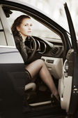 Beautiful young woman sitting in a car — Stock Photo