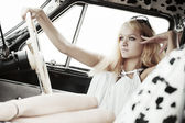 Young blond woman relaxing in a retro car — Stock fotografie