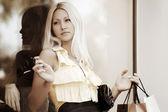 Jovem mulher contra uma montra de loja — Fotografia Stock