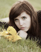 Sad young woman lying on the grass — Stock Photo