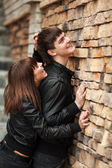 Happy young couple in leather jackets at the brick wall — Stock Photo