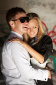 Happy young couple in love at the grungy wall — Stock Photo