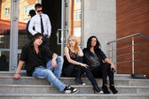 Young people sitting on the steps — Stock Photo