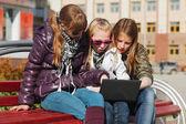 Teenage school girls using laptop on the bench — Stock Photo