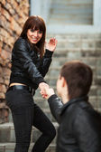 Happy young couple in leather jackets at the brick wall — Foto Stock