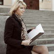 Young business woman with notebook sitting on the steps — Stock Photo #45226359