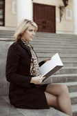 Young business woman with notebook sitting on the steps — Stock Photo