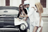 Young tourists with a road map at the retro car — Stock Photo