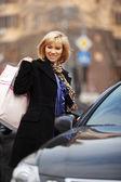 Jovem mulher com sacos de compras no carro — Foto Stock