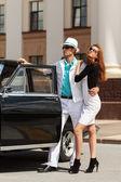 Young fashion couple at the retro car — Photo