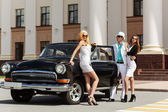 Young fashion people at the retro car — Stock Photo