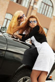 Two young fashion women at the retro car — Stock Photo