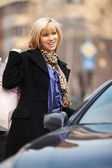 Young woman with shopping bags at the car  — Stock Photo