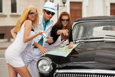 Young fashion people with a road map at the retro car  — Stockfoto