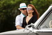 Young fashion couple at the classic car  — Stock Photo