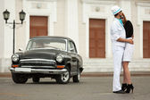 Young fashion couple in love at the retro car — Stock fotografie