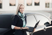Young businesswoman using laptop on a car parking — Stock Photo