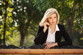 Young business woman calling on the cell phone in a city park — Stockfoto