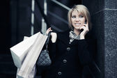 Blond woman with shopping bags calling on the phone — Stock Photo