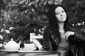 Young woman drinking tea at sidewalk cafe — Stok fotoğraf
