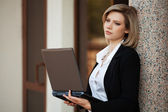 Young business woman with laptop at the office building — Stok fotoğraf