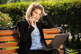 Young business woman with laptop calling on the cell phone  — Stock Photo