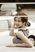 Happy young woman against a car parking — Foto Stock