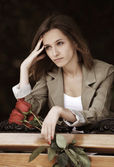 Sad young woman with a roses — Stock Photo
