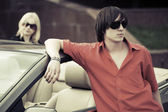 Young fashion couple at the convertible car — Stock Photo