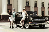 Young fashion people at the retro car — Stock fotografie