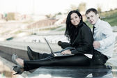 Young business man and woman using laptop outdoor — Stock Photo