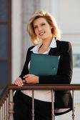 Happy young business woman with a folder at the office building — Stok fotoğraf