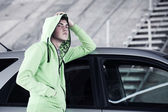 Young man standing against a car — Stock Photo