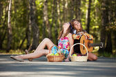 Two hippie girls with guitar in a summer forest — Stock Photo