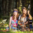 Two hippie girls with guitar in a summer forest — Stock Photo #49949063