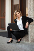 Young business woman with laptop at the office building — Zdjęcie stockowe