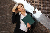 Happy young business woman with a folder at the office building — Stockfoto