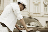 Young fashion man with a road map at the retro car — Stock Photo