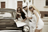 Young fashion people with a road map at the retro car — Stock Photo