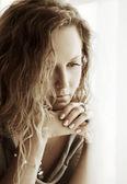 Sad beautiful woman looking through the window — Stock Photo