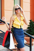 Young fashion woman with shopping bags calling on phone — Stock Photo