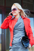 Young fashion woman calling on cell phone against office windows — Stockfoto