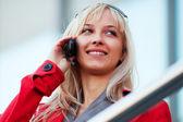Młoda kobieta moda dzwoniąc na telefon komórkowy przed oknami biura — Zdjęcie stockowe